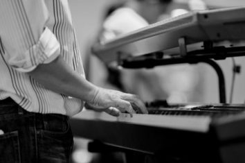 man playing on two connected MIDI keyboards