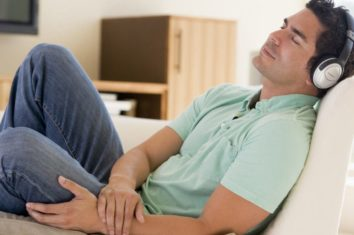 man sleeping while listening to his noise-canceling headphones