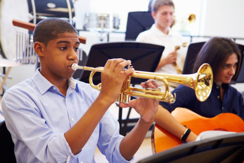 high school boy playing his student trumpet