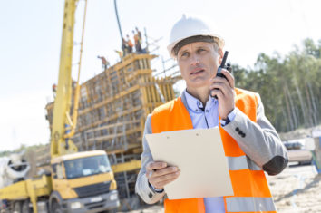supervisor using a two way radio on a construction site
