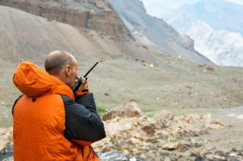 man out in the mountains using his two-way radio