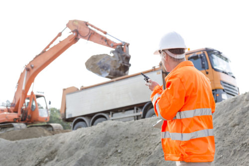 man using a two-way radio to communicate to someone far away on construction site