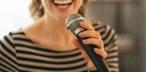 A young woman singing into a dynamic microphone