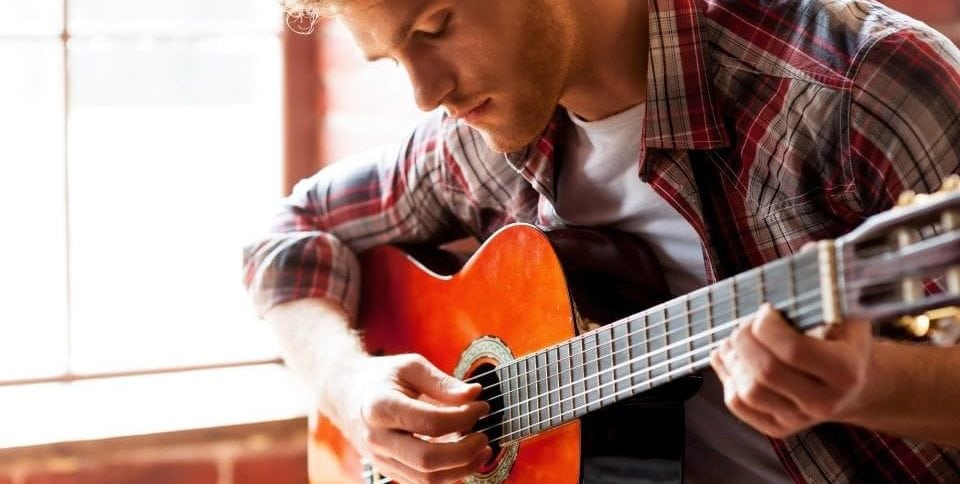 A handsome man playing an acoustic guitar