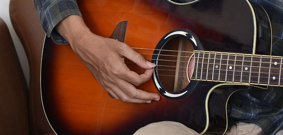 Close up of a man playing an acoustic guitar