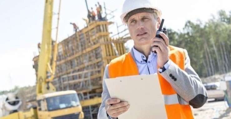 Supervisor using walkie-talkie while holding clipboard at construction site