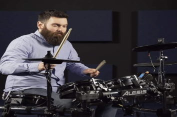 A bearded man playing an electronic drum set