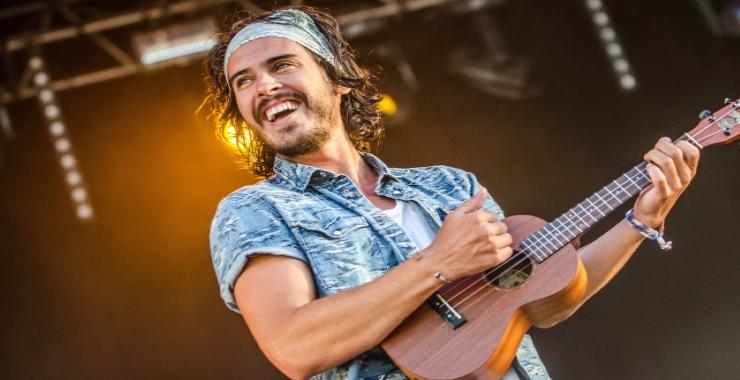 a guy playing the ukulele cheerfully