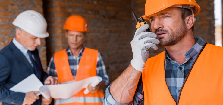 a man communicating with his team by two way radio