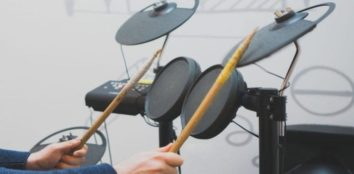 a man playing electric drums with his drumsticks