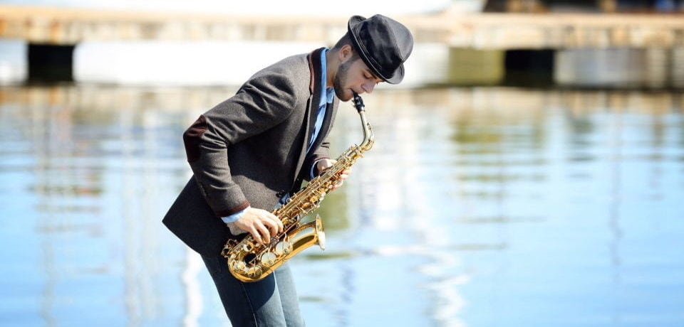 a man playing the saxophone near the sea
