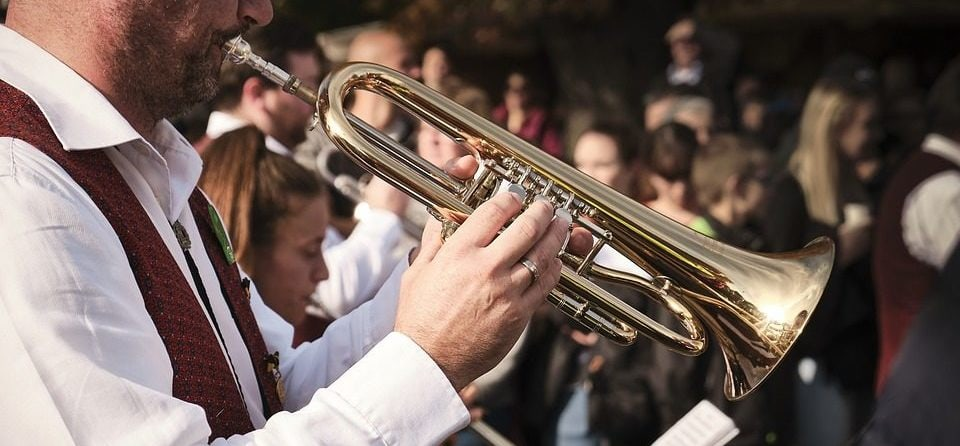 a man playing the trumpet with his hands