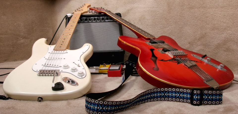 A white and a red electric guitar together next to an amp