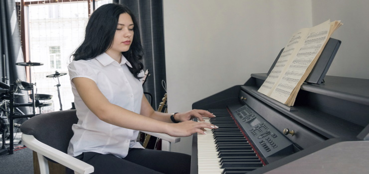 a woman playing a digital piano inside a room