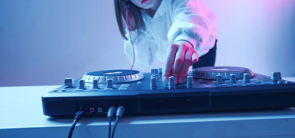 a woman playing a dj controller on a white table