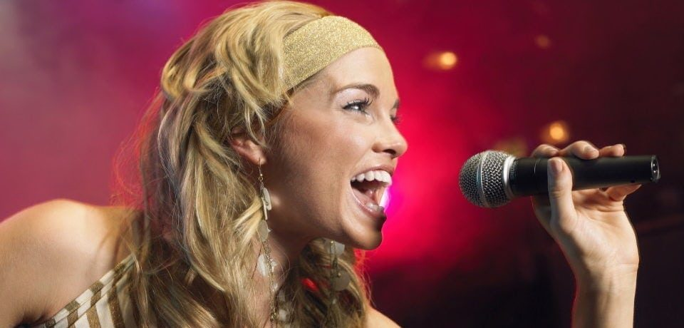 a woman singing with her wireless microphone