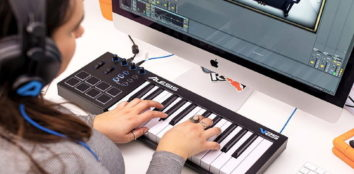A woman using her midi keyboard with her computer