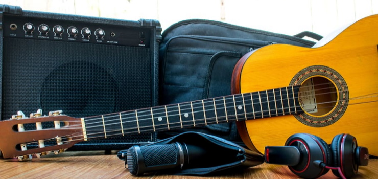 an amplifier and an acoustic guitar on the floor