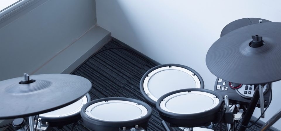 an electric drum set in a room near the window