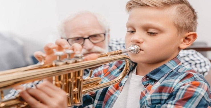 boy learning how to play the trumpet