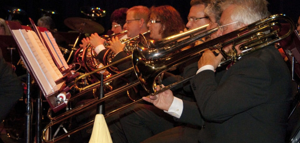 five people playing the trombones
