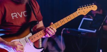 A man playing a brown and white electric guitar