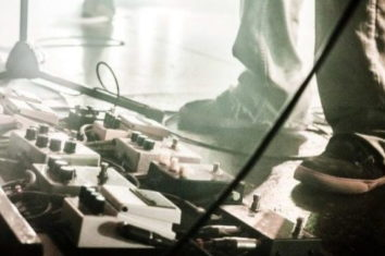 multiple guitar pedals set up on the floor during a gig