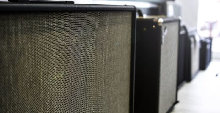 row of different guitar and keyboard amplifiers